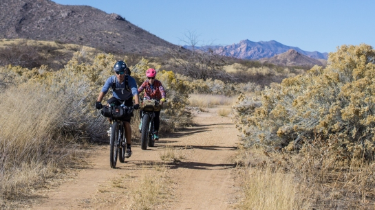 Kody and Jenny roll through another road lined with cottony desert brush.
